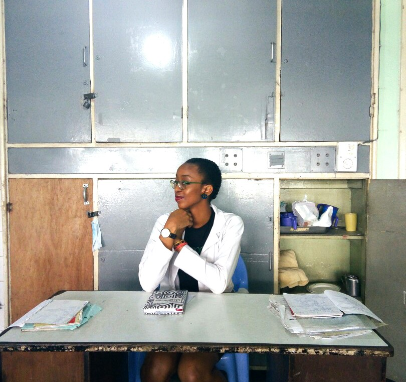 Housemanship In Nigeria (LUTH) Chronicles, Nigerian blogger Cassie Daves sitting at a desk in hospital holding cassie daves blog planner