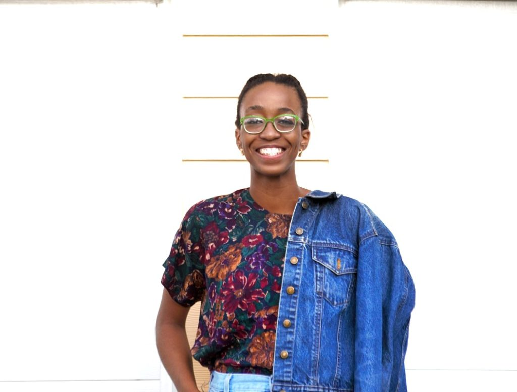Styling high waisted denim mom shorts, Portrait image of Nigerian fashion blogger Cassie Daves wearing denim jacket and a wide smile