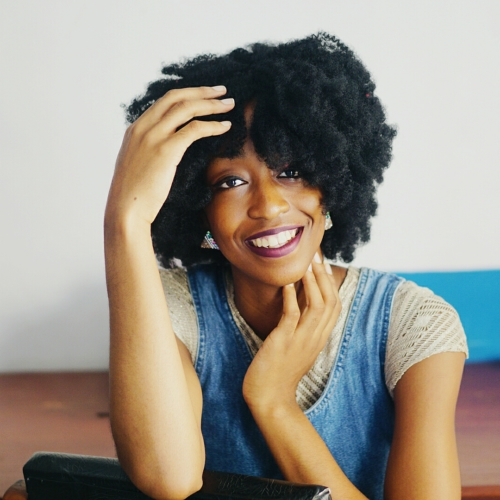 Nigerian Fashion and lifestyle blogger Cassie Daves in big fro smiling broadly