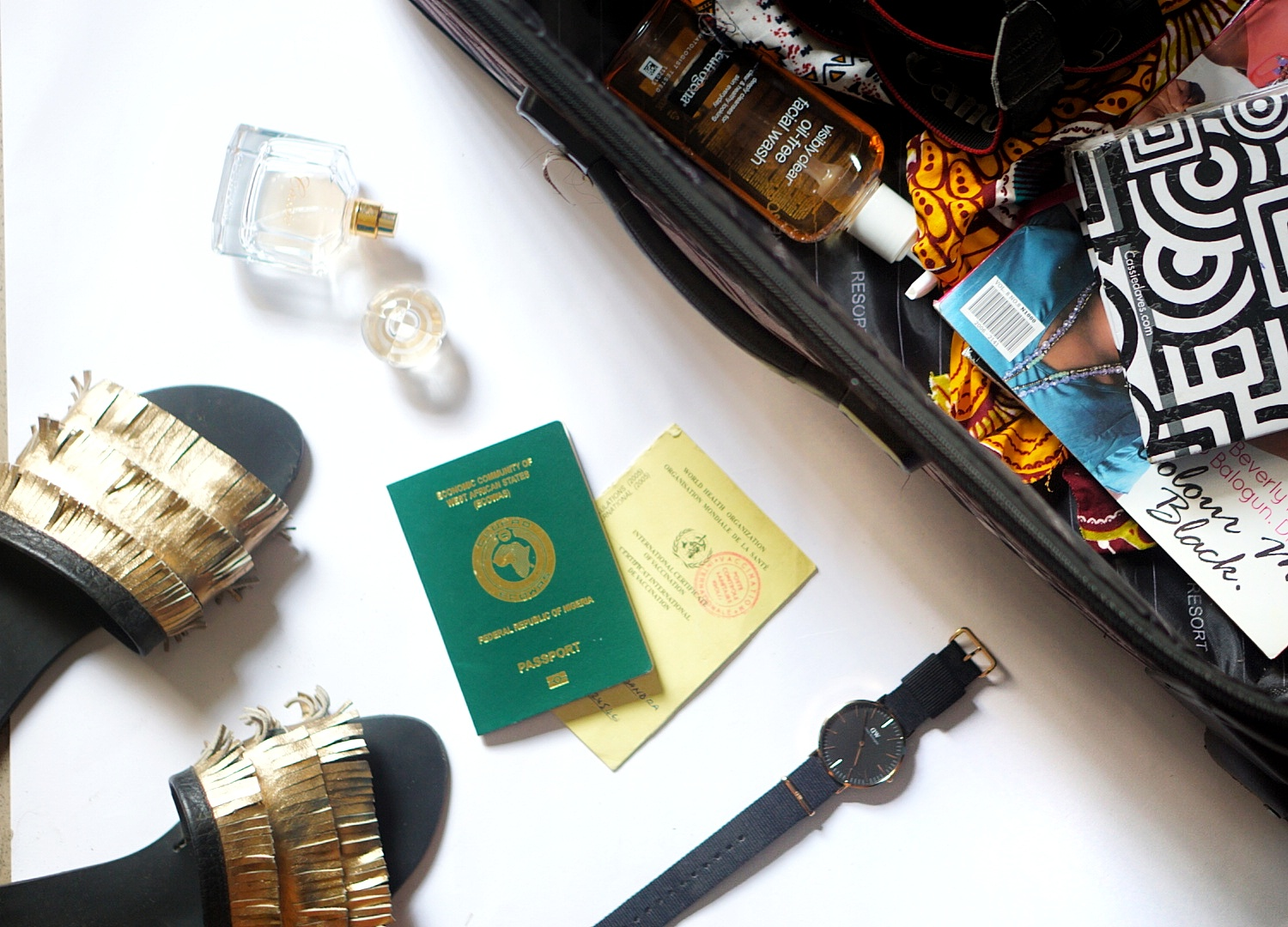 Flat lay image of travelling bag and other essentials for road trip to Ghana : passport and yellow card
