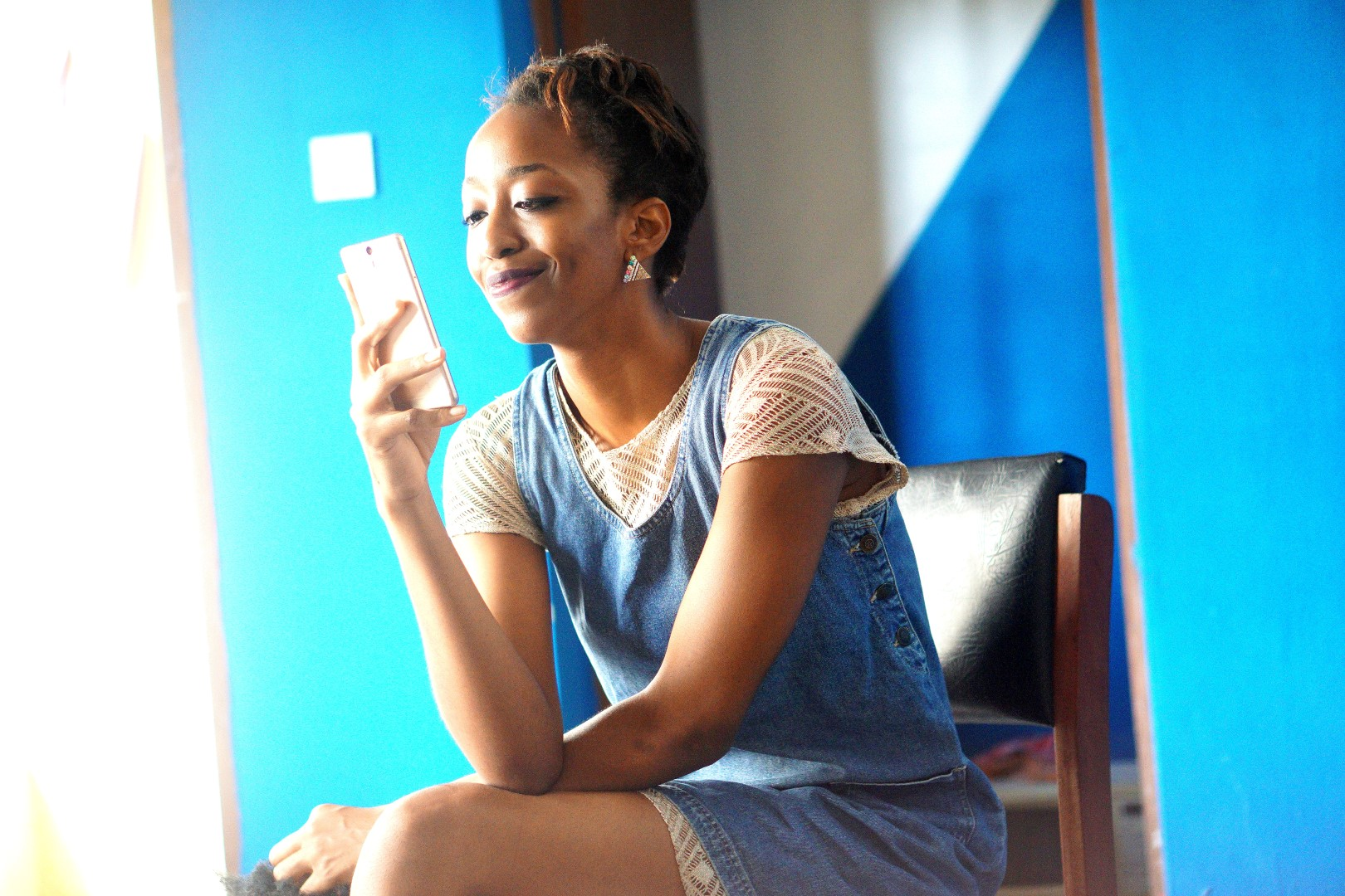 updated blogging process , Nigerian fashion and lifestyle blogger cassie daves looking into a phone screen