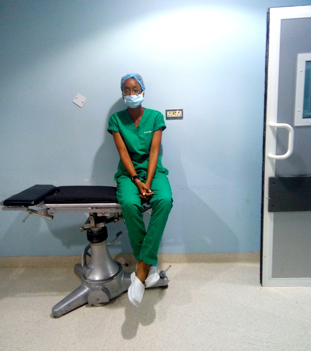housemanship in nigeria, Nigerian blogger and medical doctor cassie daves in scrubs sitting in the modular theatre