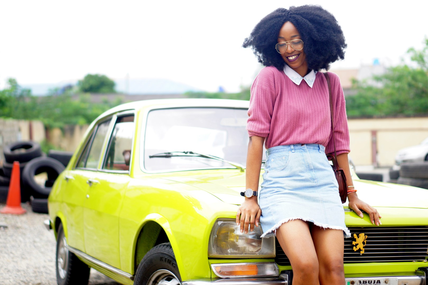 nigerian fashion blogger Cassie daves wearing a denim mini skirt, mauve sweat shirt. leaning against a lemon green peugeot 504