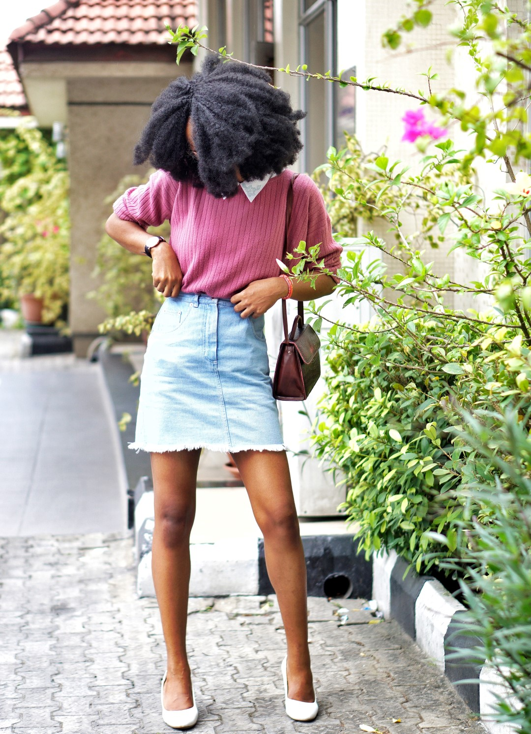 nigerian fashion blogger Cassie daves wearing a denim mini skirt, sweat shirt and white court shoes