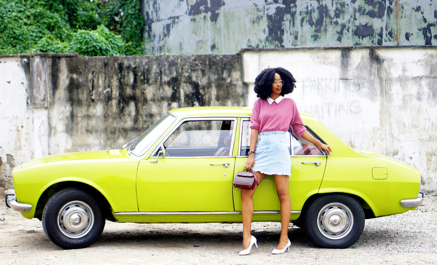 nigerian fashion blogger Cassie daves wearing a denim mini skirt. leaning against a lemon green peugeot 504