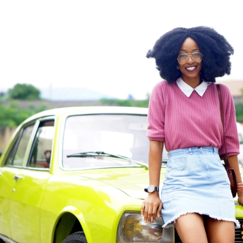 nigerian lifestyle blogger Cassie daves wearing a denim mini skirt. leaning against a lemon green peugeot 504