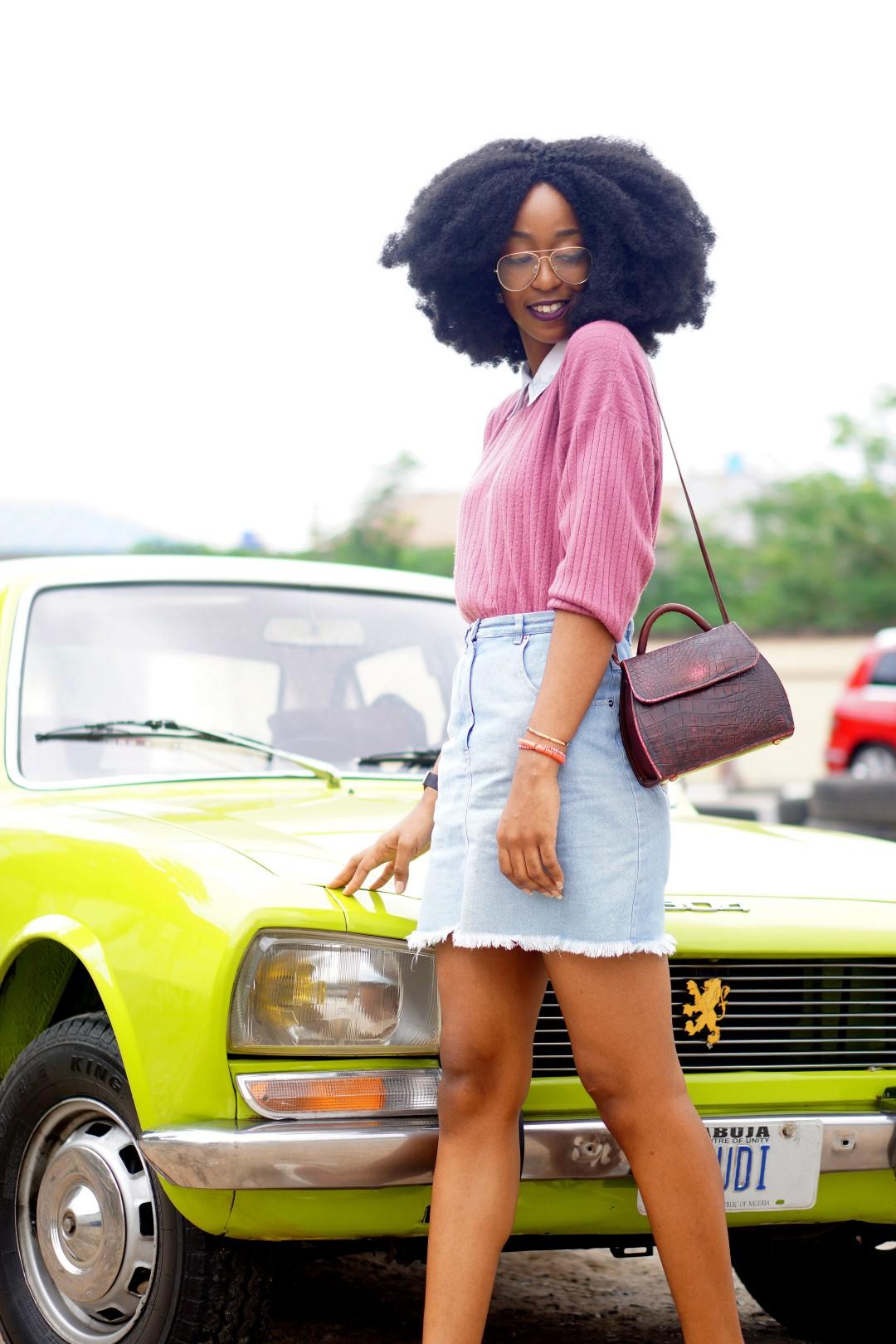 nigerian blogger Cassie daves wearing a denim mini skirt, mauve sweat shirt. leaning against a lemon green peugeot 504