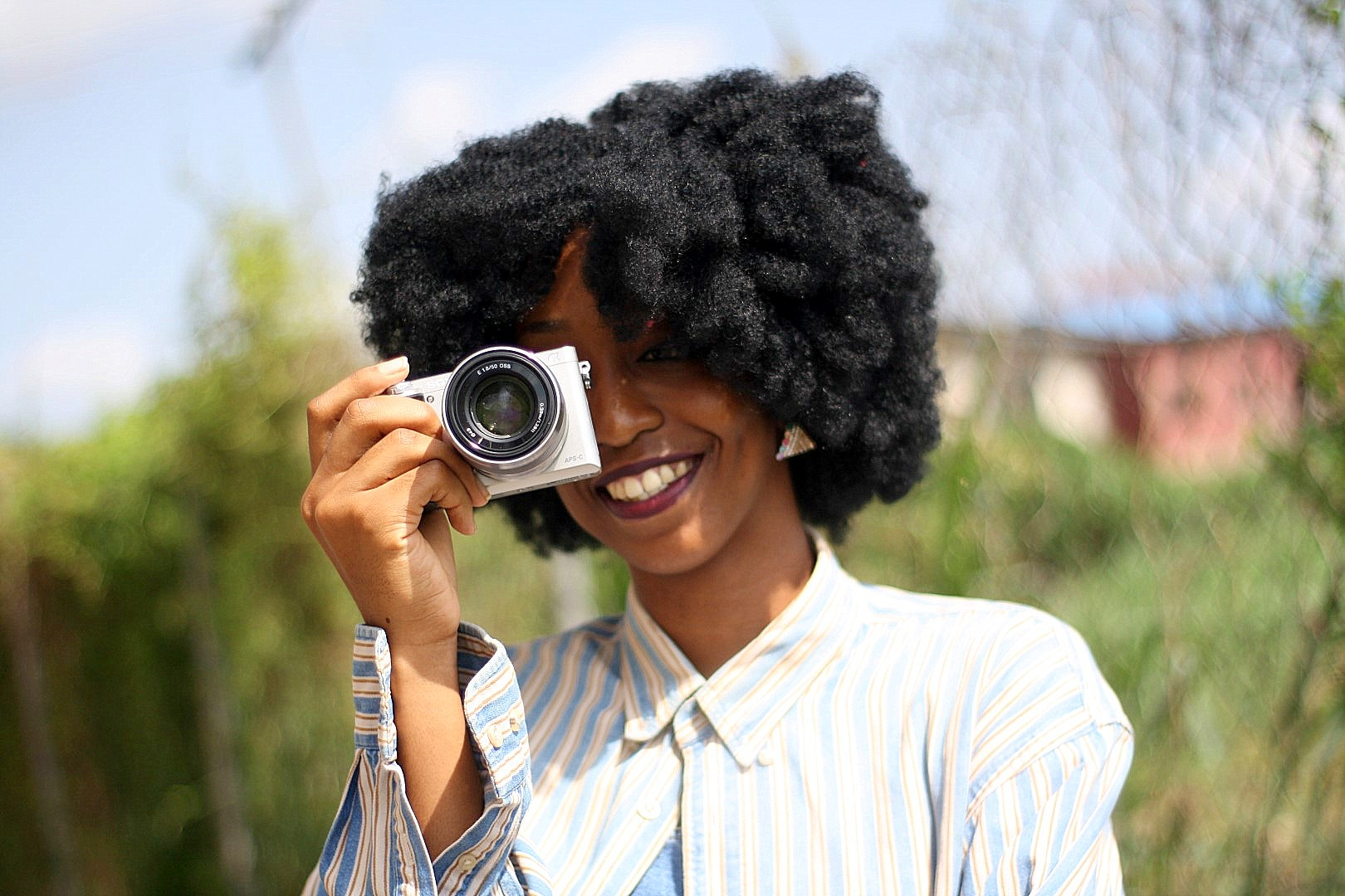 Nigerian lifestyle blogger cassie daves holding the Sony a6000 camera