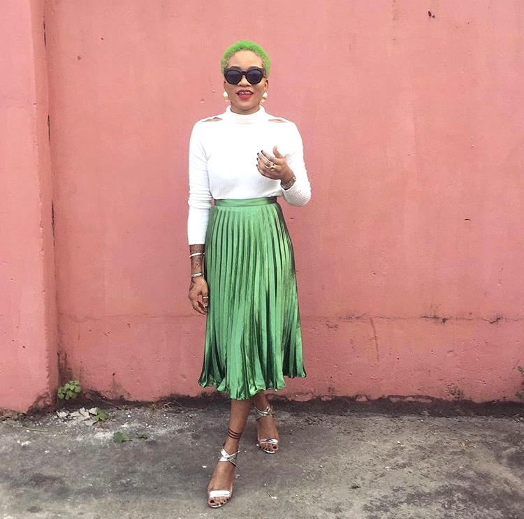 Nigerian fashionista jennifer oseh, theladyvhodka in a green mettalic pleated skirt and white turtle neck top