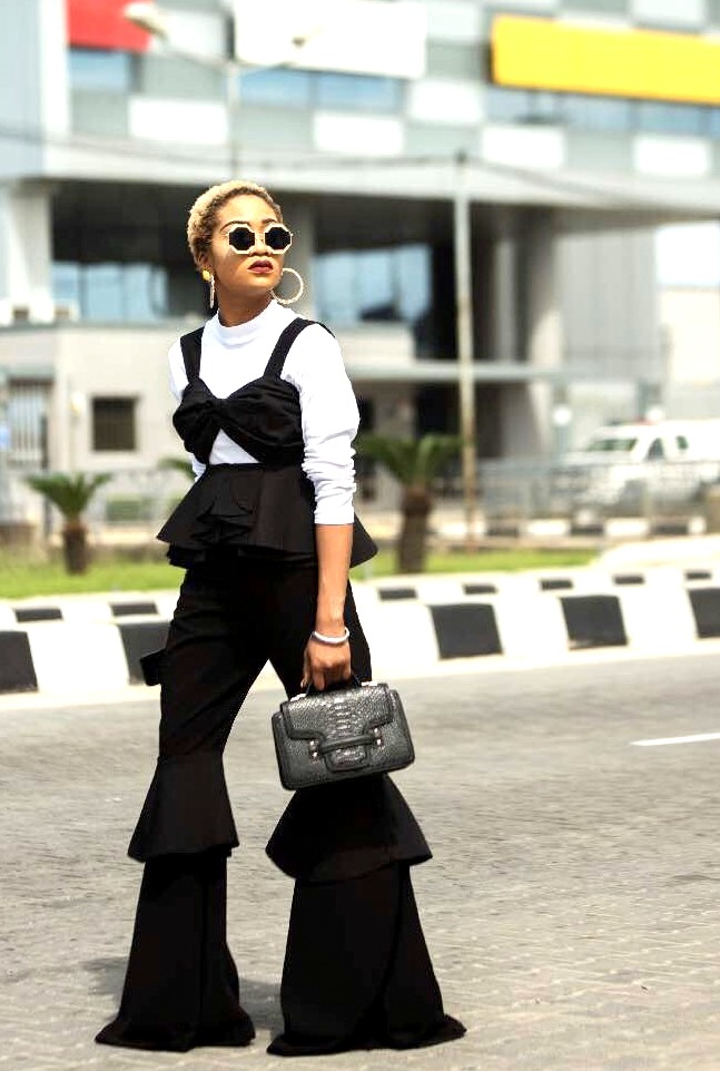Nigerian style influencer jennifer oseh, theladyvhodka in a black ruffled pants layered with a white turtle neck top