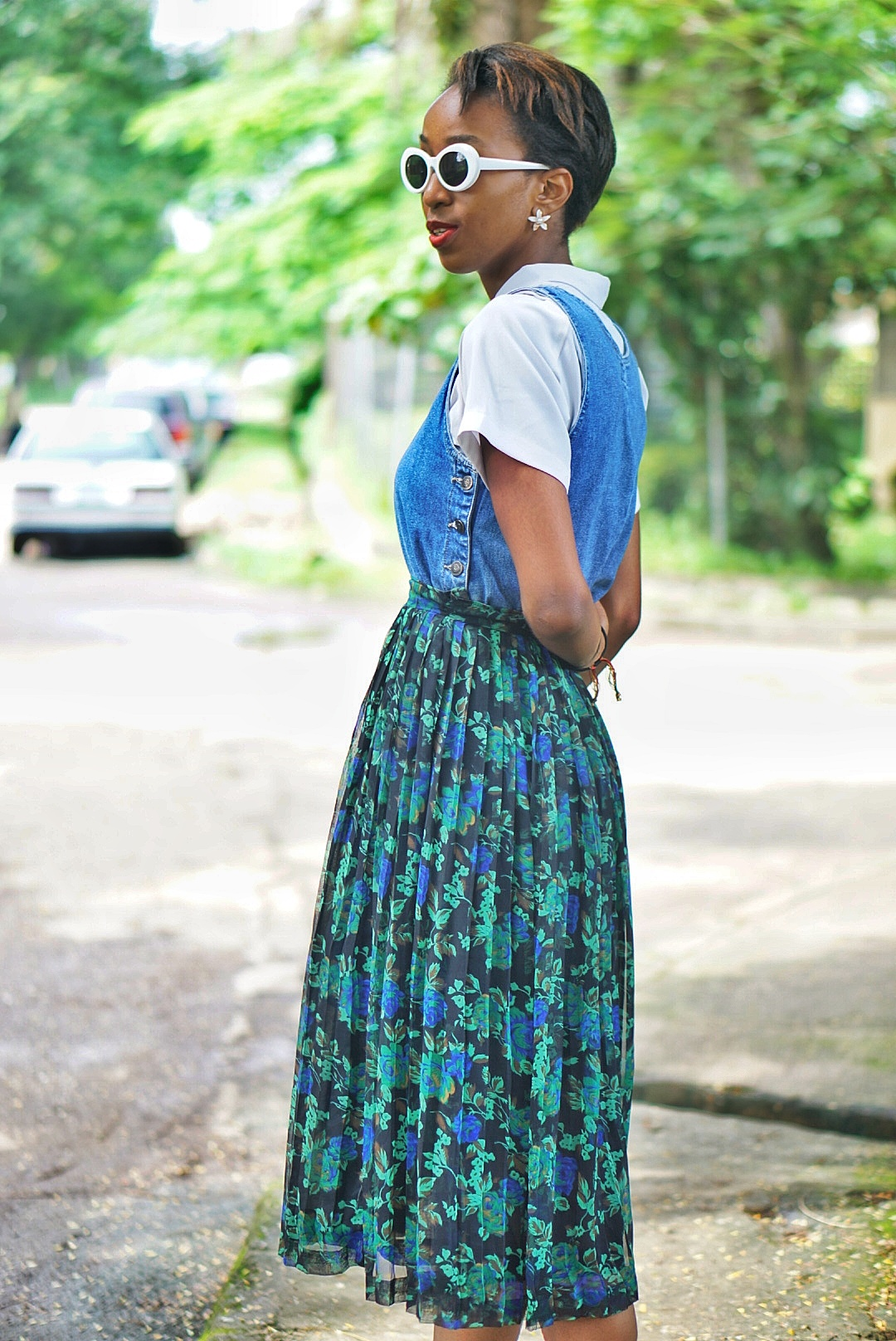 Nigerian fashion blogger Cassie Daves in prints pleated midi skirt and a denim dress layered on a white shirt