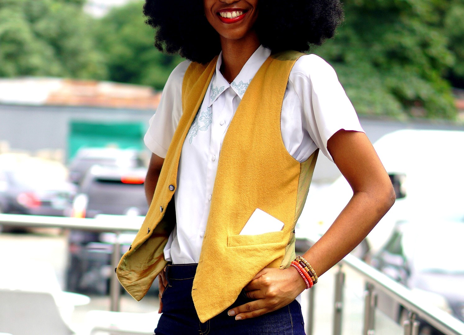 Nigerian Fashion blogger Cassie Daves wearing a mustard waistcoat and white shirt.