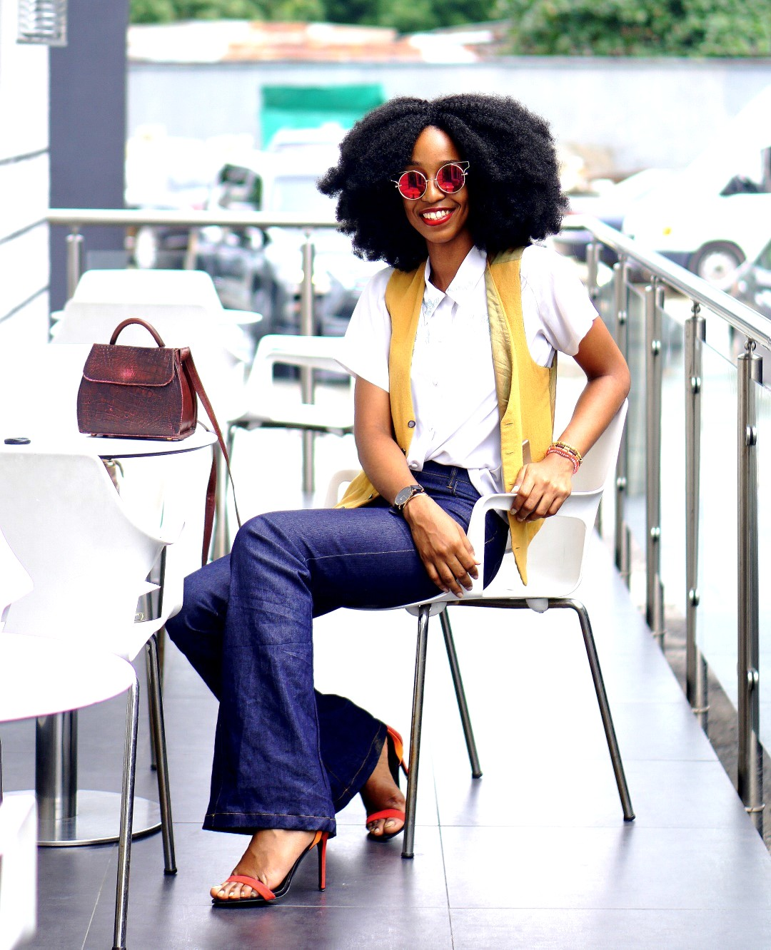 Nigerian Fashion blogger Cassie Daves in a high waisted flare jeans, mustard waist coat and white shirt