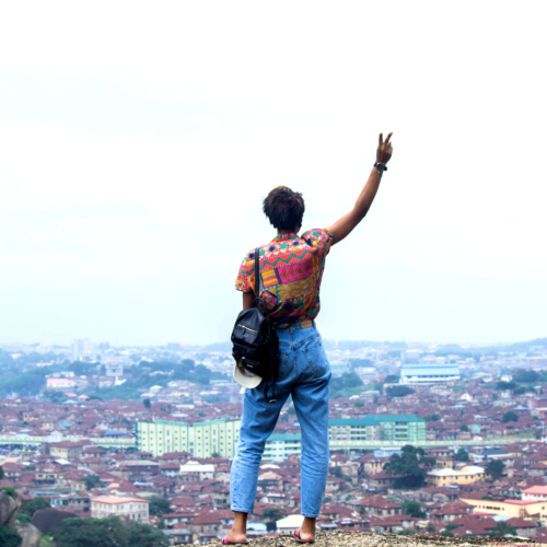 Nigerian lifestyle blogger Cassie Daves standing on the olumo rock in Abeokuta giving a peace sign