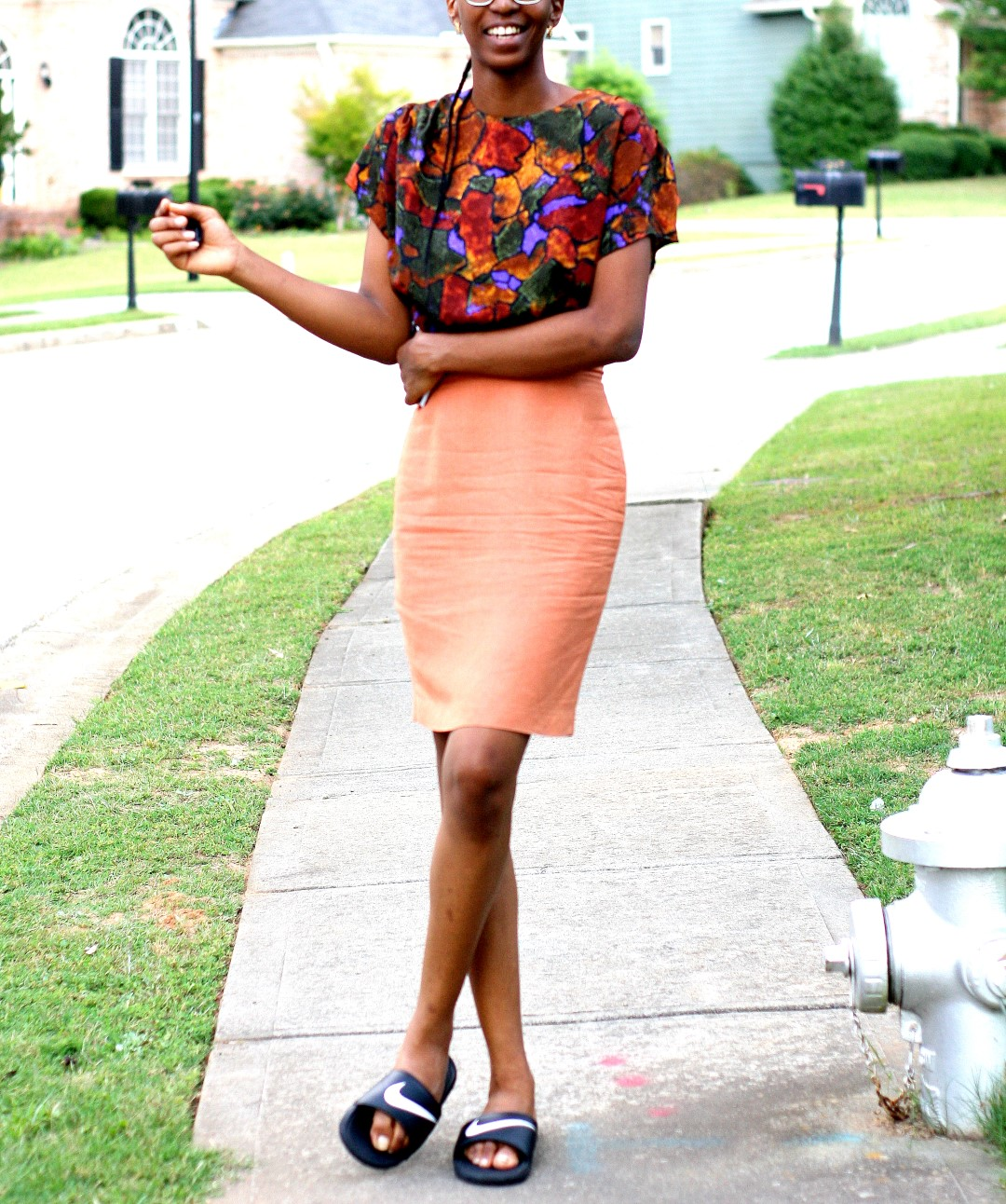 Nigerian fashion blogger Cassie Daves in a profile shot wearing a bright coloured prints top, orange skirt and nike slides