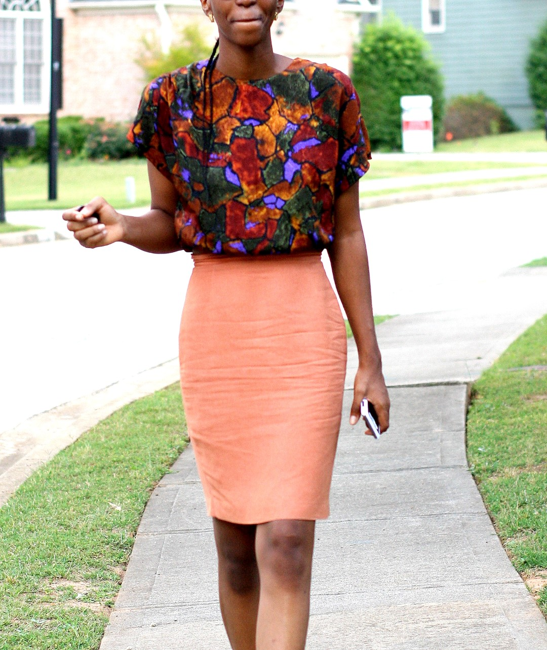 Going back to the basics - Nigerian fashion blogger Cassie Daves in a profile shot wearing a bright coloured prints top, orange skirt in atlanta