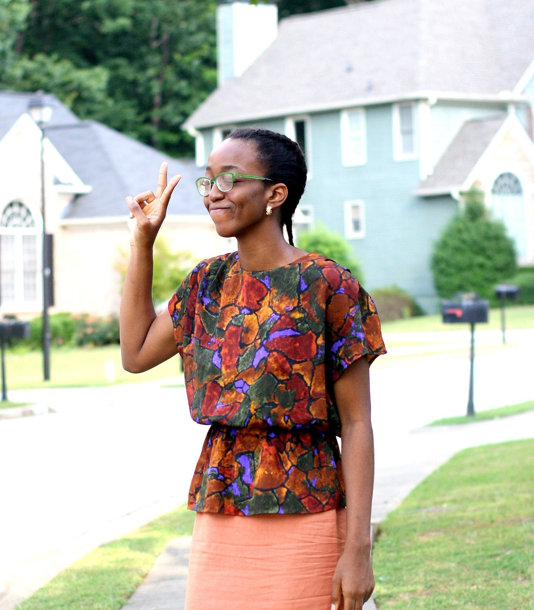 Going back to the basics - Nigerian fashion blogger Cassie Daves in a profile shot wearing a bright coloured peplum prints top and orange skirt