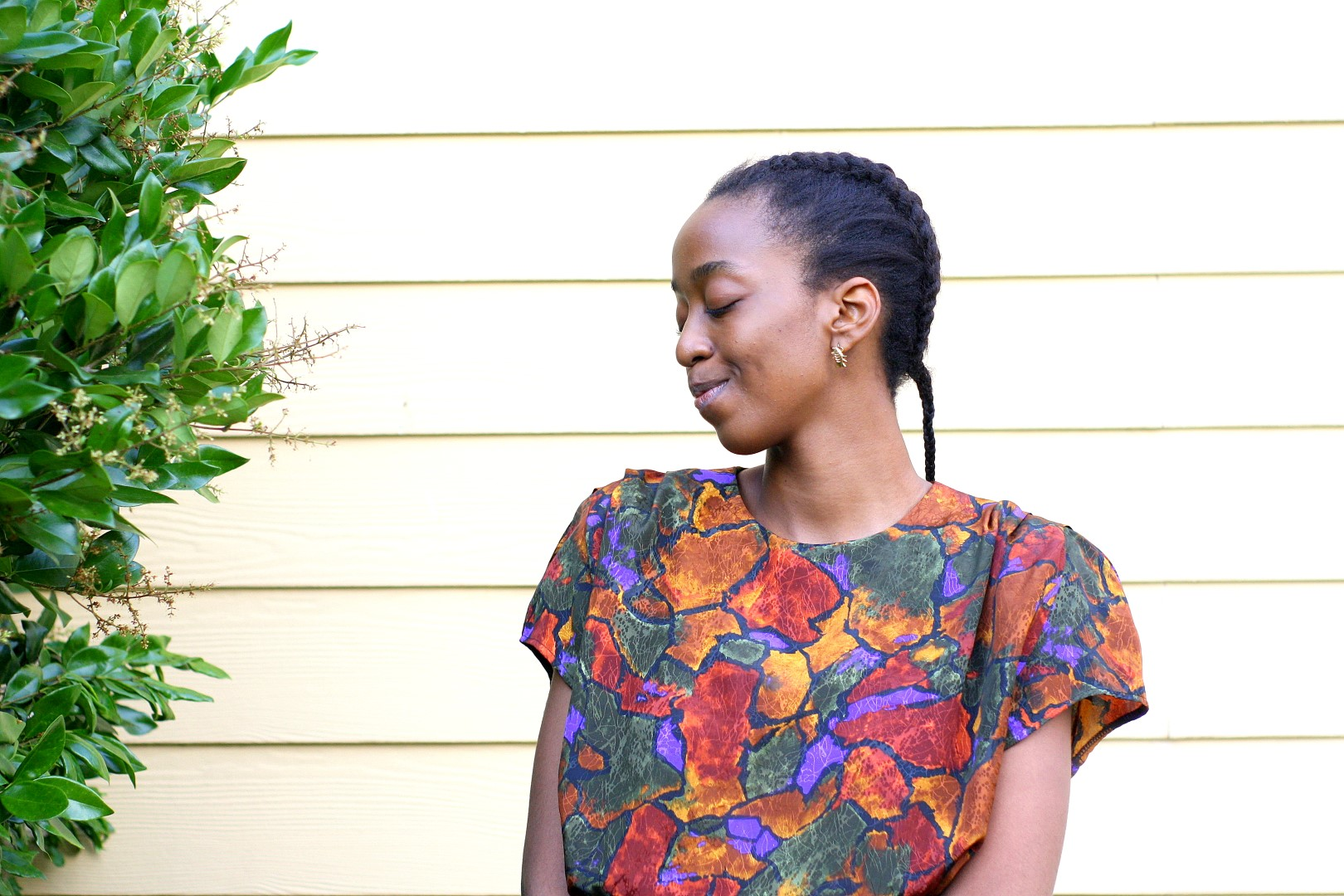 Going back to the basics - Nigerian fashion blogger Cassie Daves in a profile shot wearing a bright coloured prints top