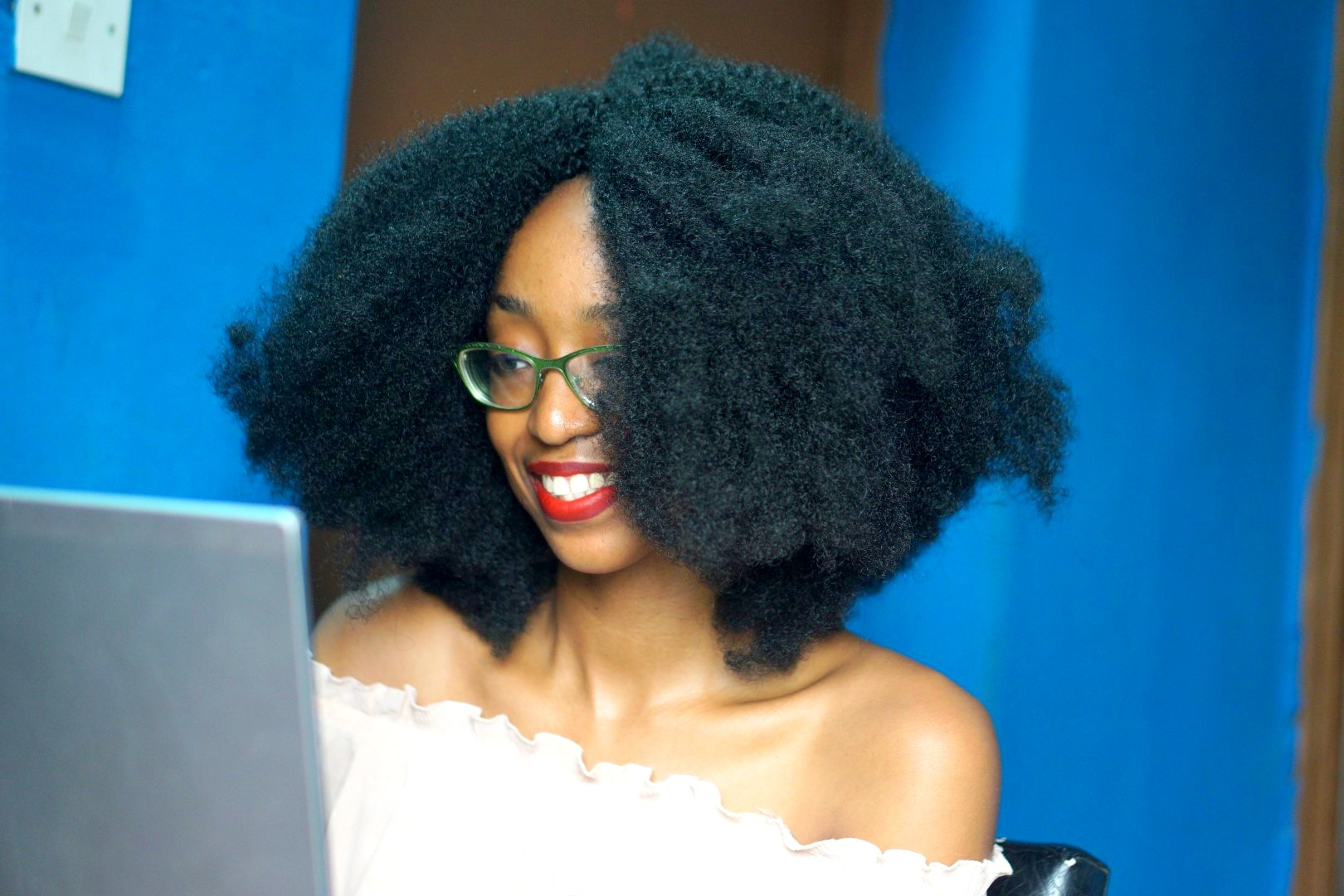 Nigerian fashion blogger Cassie Daves sitting in front of a laptop sharing why she moved from blogger to wordpress