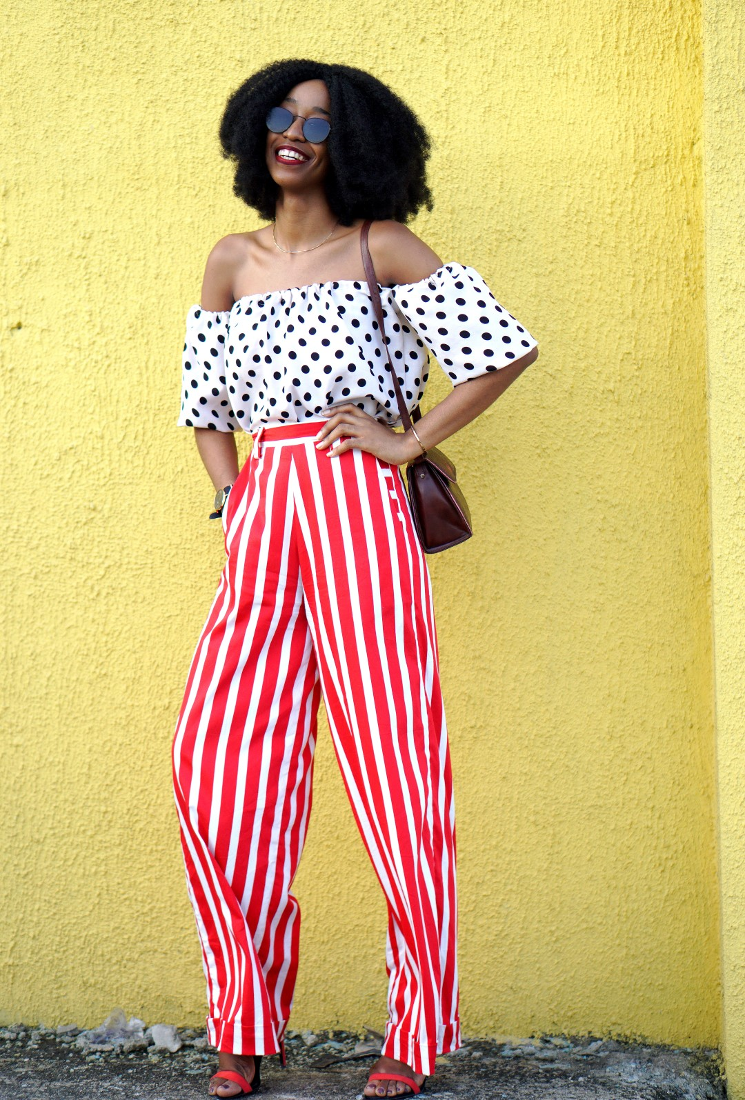 Mixed prints fashion trend : Nigerian fashion blogger Cassie Daves In a polka dot off shoulder top and striped pants and sunglasses