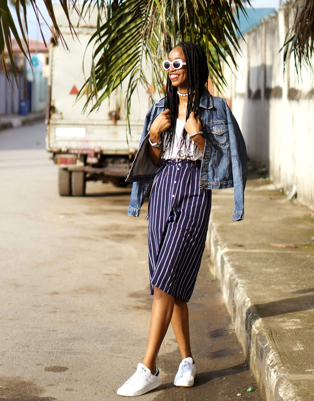 Nigerian blogger cassie daves styling the skirt and sneakers trend, denim jacket and kurt cobain sunglasses