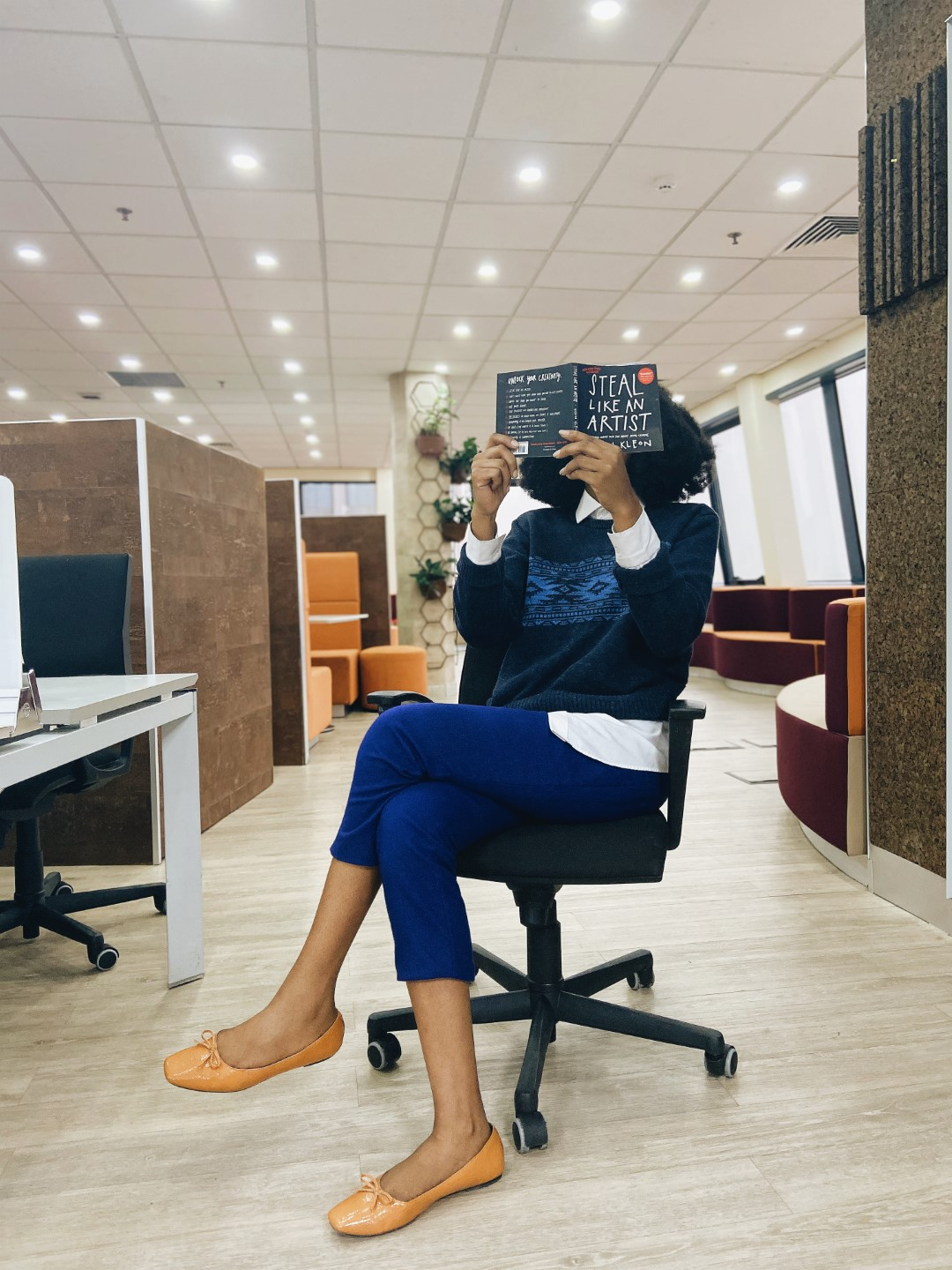 Cassie Daves Nigerian blogger in blue sweater holding the steal like an artist book