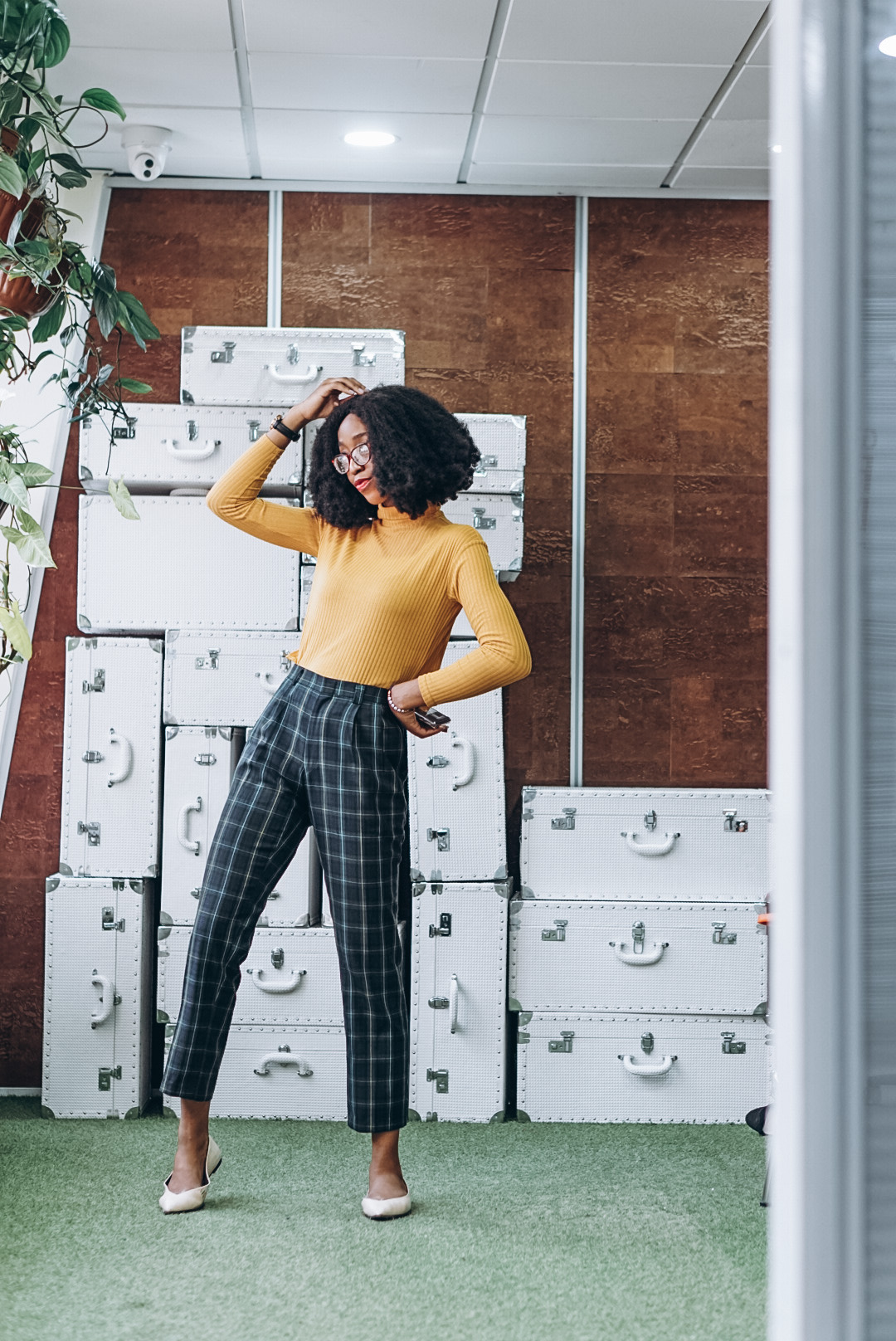Nigerian fashion blogger Cassie Daves wearing a yellow turtle neck and blue - green plaid cropped pants